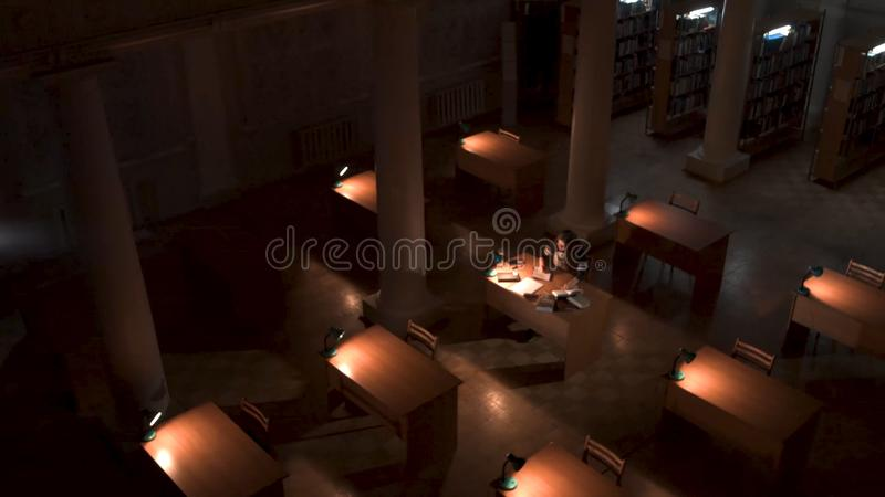 Top view of student hand writing a book with laptop at library. Girl sitting in empty library at night top view stock photography