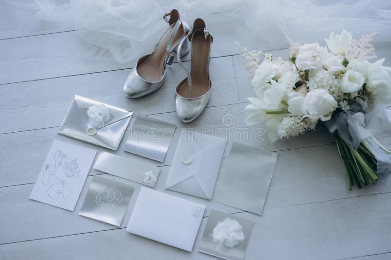 Top view of stylish wedding invitations with bridal shoes and bouquet. On floor royalty free stock images