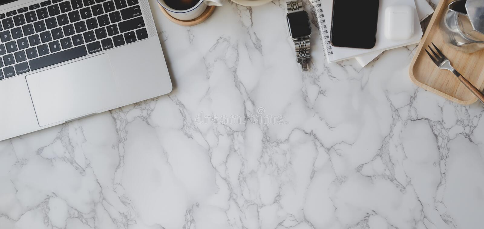 Top view of stylish workspace with laptop computer and office supplies on marble desk royalty free stock photos