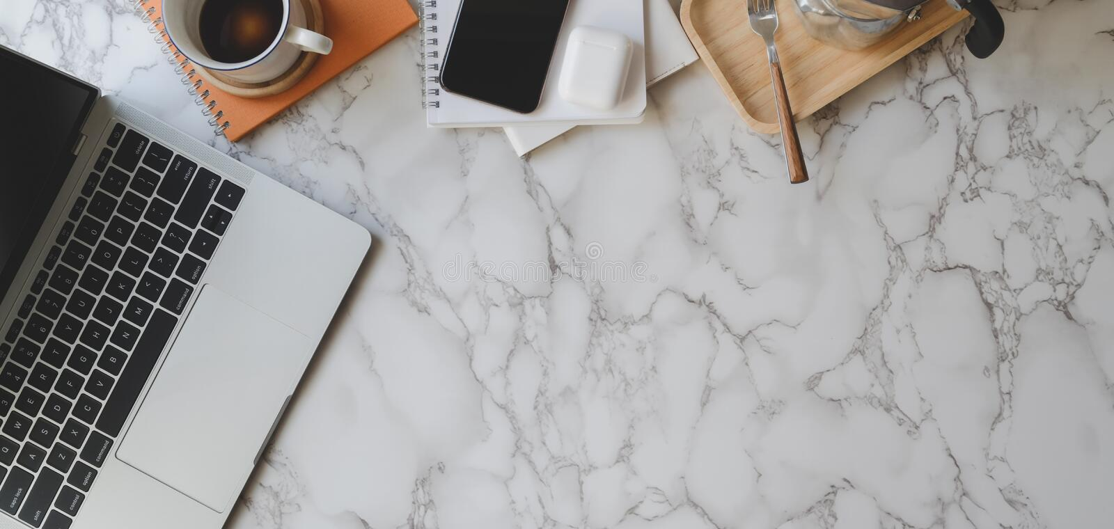 Top view of stylish workspace with laptop computer and office supplies on marble desk royalty free stock photography
