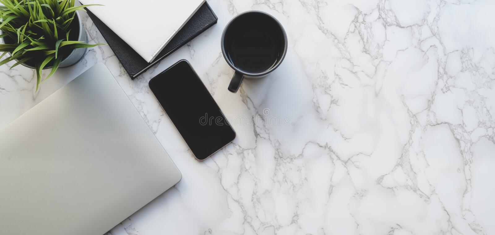 Top view of stylish workspace with laptop computer and office supplies on marble desk royalty free stock images