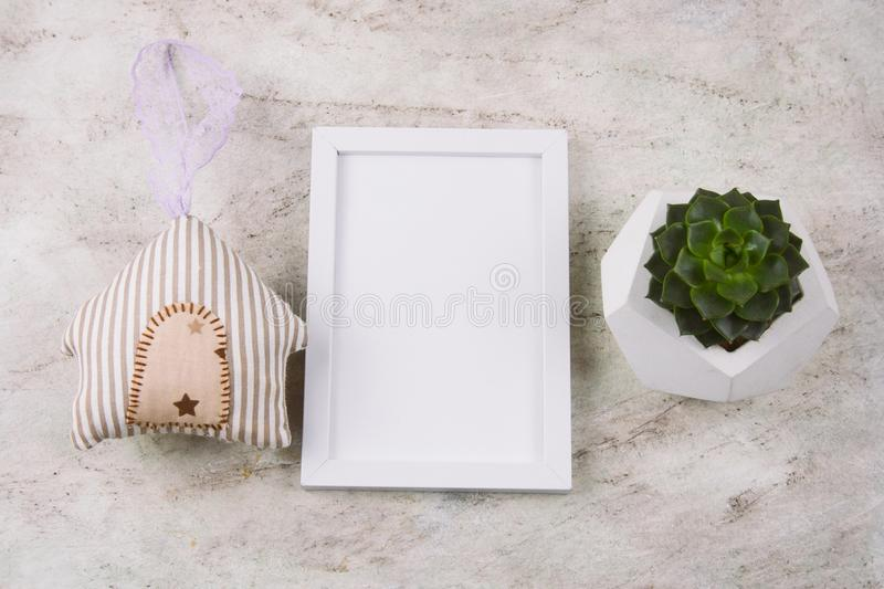 Succulent in concrete pot , stuffed toy house and white mock up frame. Top view succulent in concrete pot , stuffed toy house and white mock up frame on a marble stock photography