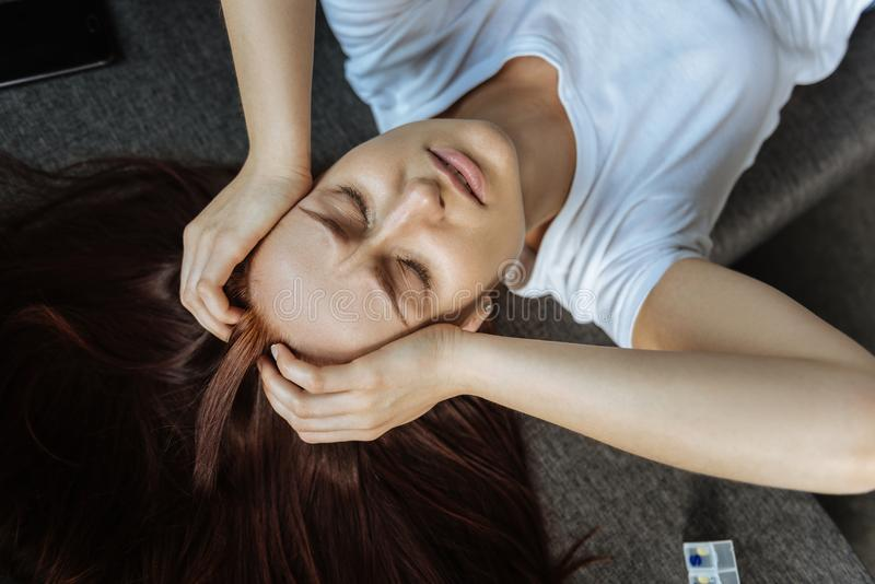Top view of a suffering woman closing her eyes. Unbearable pain. Top view of a sad unhappy suffering woman closing her eyes and holding her head while suffering royalty free stock images