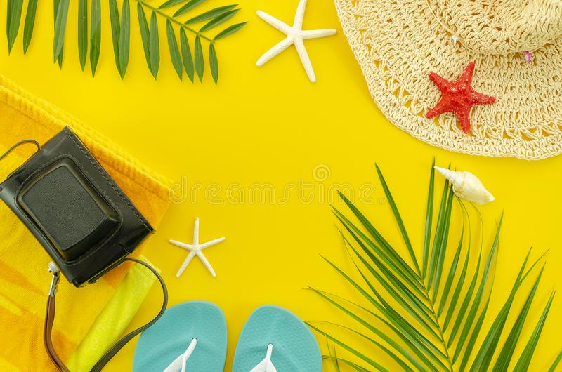 Top view summer beach accessories. Frame banner with tropical palm leaf branches and wicker hat on yellow background royalty free stock images