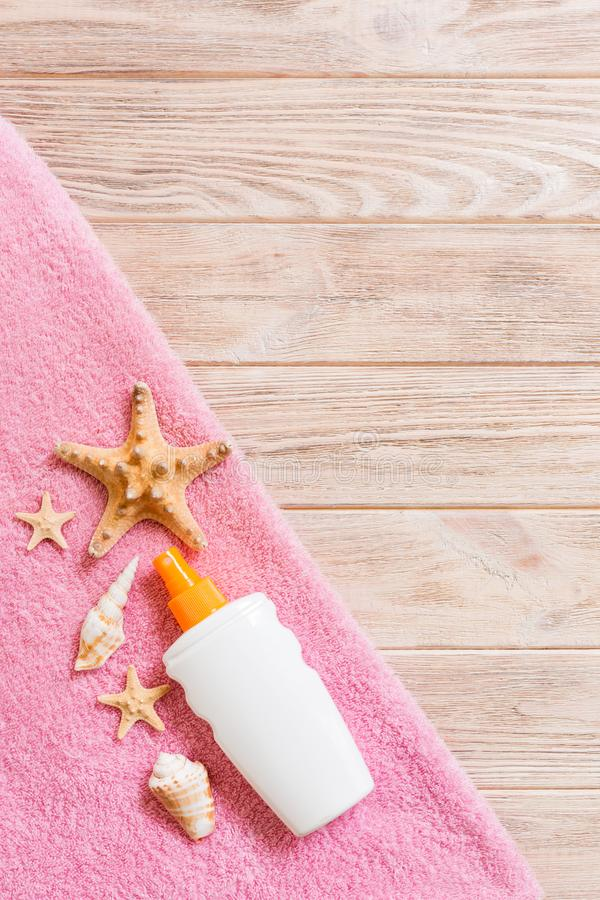 Top view of summer beach staff with copy space. Seashells or seastar, a bottle of suncream and pink towel on wooden background. stock images