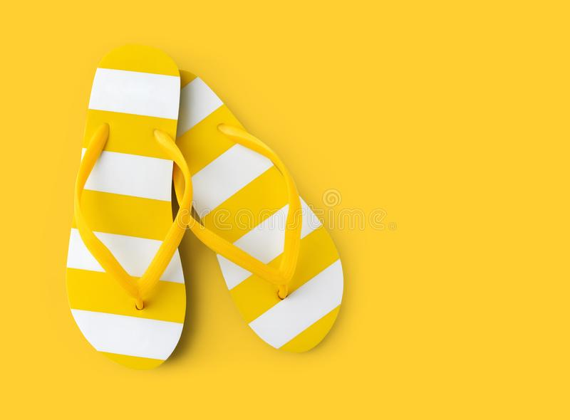 Top view of summer beach yellow striped flip flop isolated in yellow background sea holiday vacation and travel concept stock images