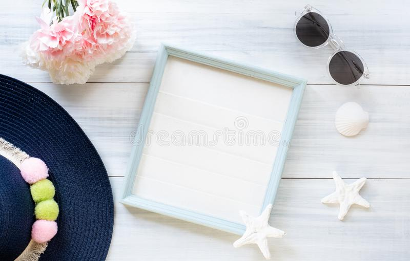 Top view of summer blue female hat and picture frame with sunglasses and seashell and star fish decoration on white wood table. stock photos