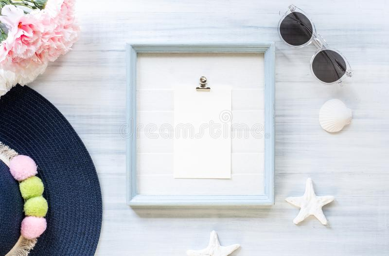 Top view of summer blue female hat and picture frame with sunglasses and seashell and star fish decoration on white wood table. stock image