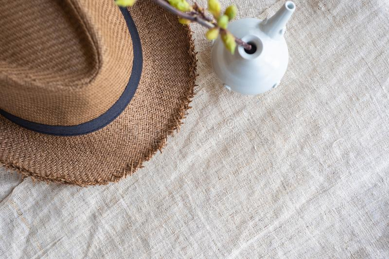 Top view of Summer brown panama straw hat with flower plant in vase on linen cloth.travel concept.copy space for adding text.  stock photo