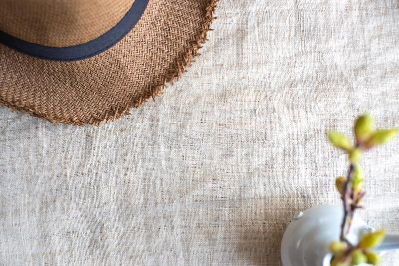 Top view of Summer brown panama straw hat with flower plant in vase on linen cloth.travel concept.copy space for adding text.  royalty free stock photography
