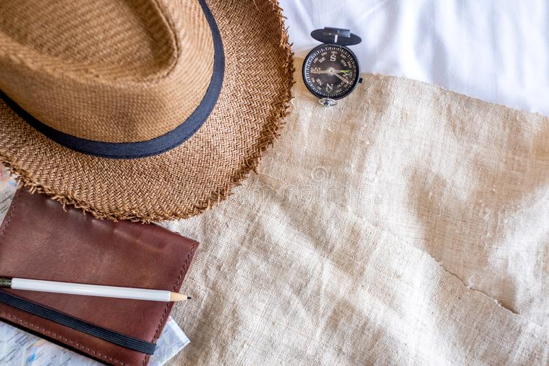 Top view of Summer brown panama straw hat,mobile,notebook map,compass on linen cloth.vacation travel concept.copy space for adding. Text royalty free stock photography