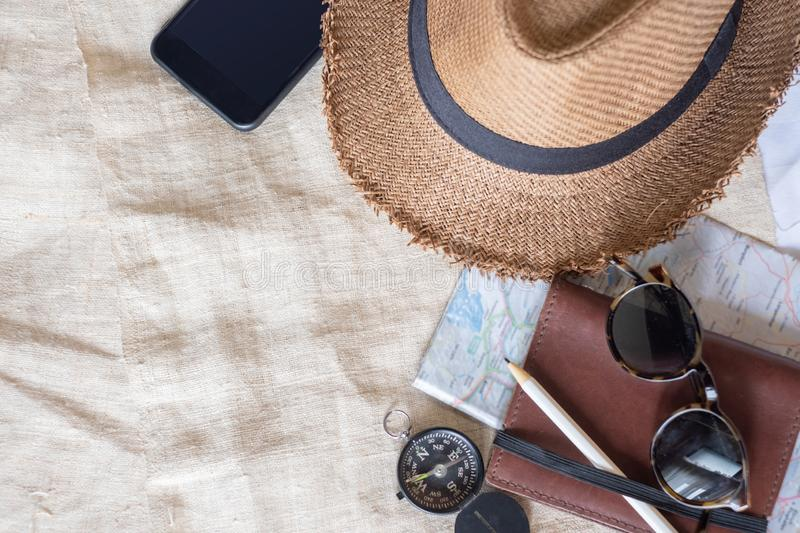 Top view of Summer brown panama straw hat,mobile,sunglasses,notebook map,compass on linen cloth.vacation travel concept.copy space. For adding text royalty free stock photos