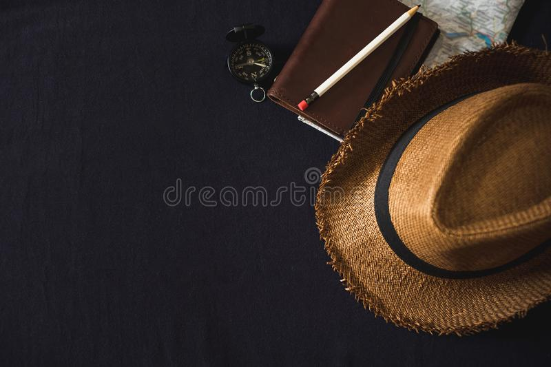 Top view of Summer brown panama straw hat,notebook map,compass o. N linen navy blue cloth.vacation travel concept.copy space for adding text stock photo