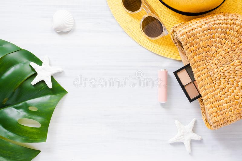 Top view summer item on white wood table.Monstera leaf and wicker bag with cosmetic.summer vacation royalty free stock photos