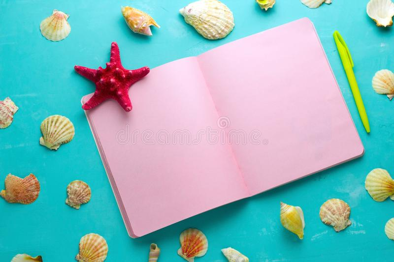 summer mock up , open notepad with blank pink paper sheets,yellow pen and seashells on a vibrant blue background royalty free stock images