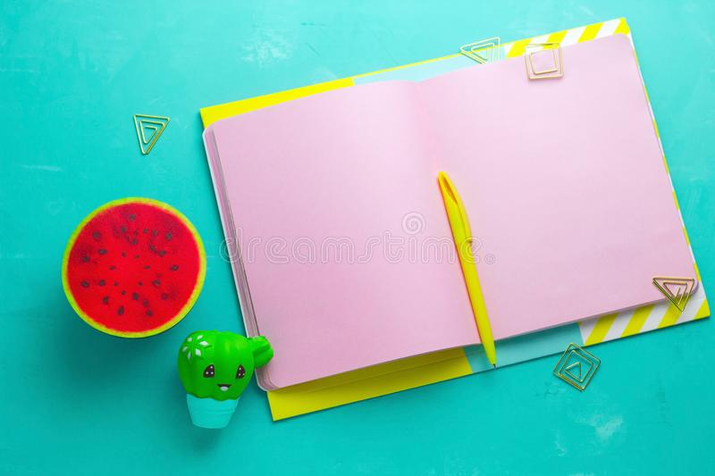 summer mock up , open notepad with blank pink paper sheets,yellow pen and squishy anti stress toy watermelon and cactus stock image