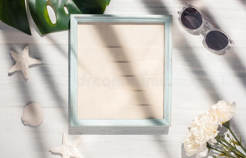 Top view summer picture frame with monstera leaf and seashell on white wood table with hard shadow light.summer vacation stock photos