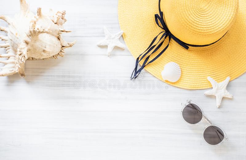 Top view of summer yellow female hat with sunglasses and shell and star fish decoration on white wood table.summer vacation stock image