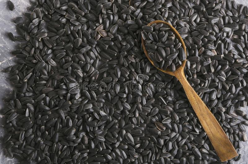 Top view of sunflower seeds and wooden spoon full of seeds. Lot of roasted sunflower seeds and wooden spoon on it Closeup of wooden spoon on the just roasted stock photo
