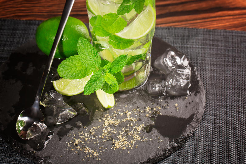 Top view of sweet mojito cocktail with a long tea-spoon, mint, ice cubes and lime segments on the black napkin. Copy space. royalty free stock images