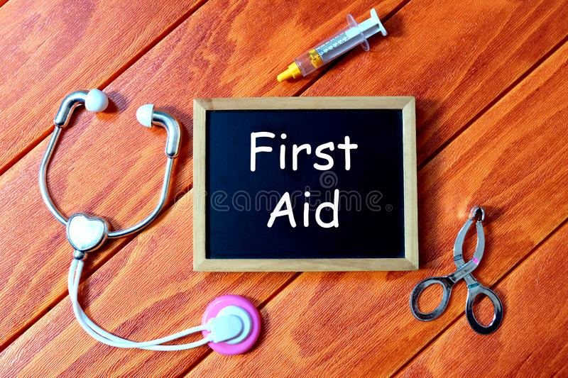 Top view of syringe,stethoscope, and blackboard written with first Aid on wooden background.Health concept. stock photography