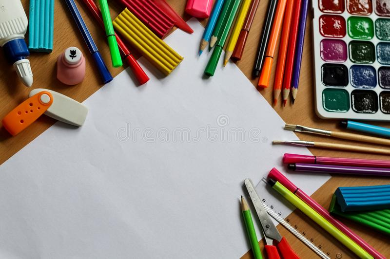 Top view on table with blank sheet of paper. Back to school concept with space for text. Color paints with paint brushes, pencils royalty free stock photos