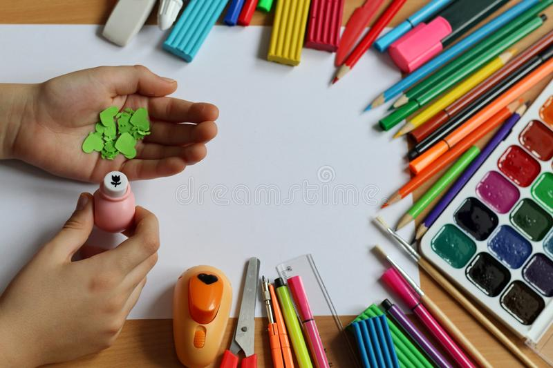 Top view of the table with a clean sheet of paper and a baby hands that make a gift. Mother`s Day and Women`s Day. Back to schoo stock images