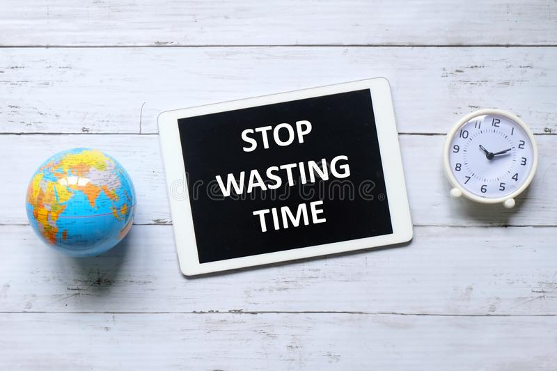 Top view of table clock,globe and tablet written with message Stop Wasting Time on wooden background. royalty free stock photography