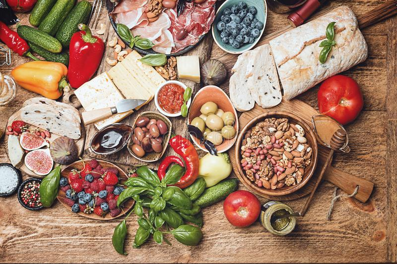 Top view table full of food. Italian antipasti wine snacks set. Cheese variety, nuts, Mediterranean olives, sauces, Prosciutto di Parma or jamon, tomatoes royalty free stock photo