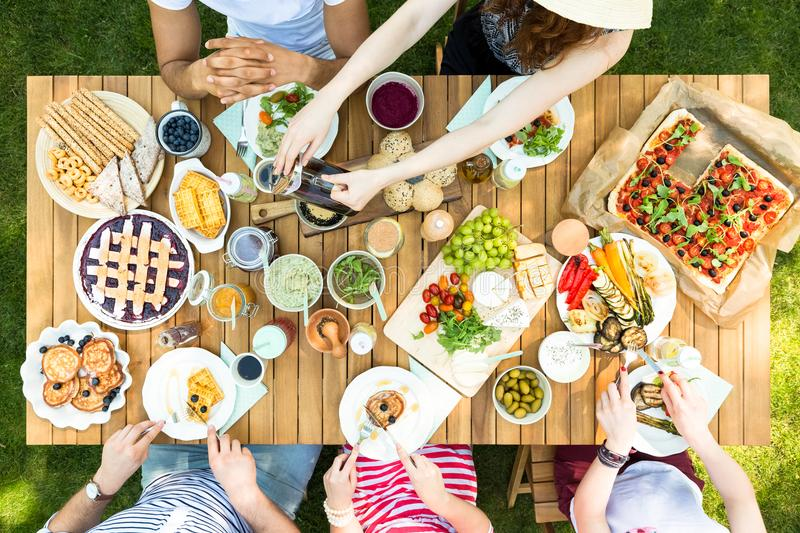 Top view of a table with Italian food and friends eating and drinking in the garden royalty free stock photo