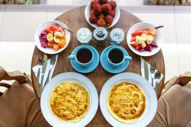 Top view, table setting. Balinese tropical breakfast of fruit, coffee and scrambled eggs and banana pancake for two. on the street royalty free stock photos