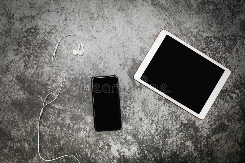 Top view Tablet and smartphone on an old gray grunge with headphones. stock image