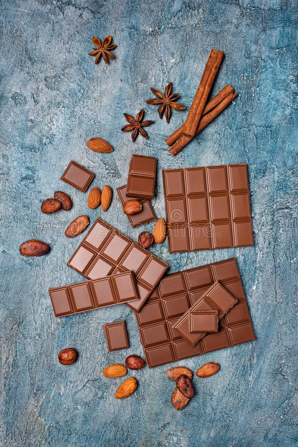 Top view of tasty broken chocolate bars with cocoa beans, nuts and spices. As ingredient for confectionery on blue concrete background royalty free stock images