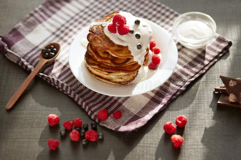 Top view of tasty pancakes with blueberries and raspberries on dark brown table, cup of tea or coffe, wooden spoon with fresh. Berry, pieces of chocholate stock photography