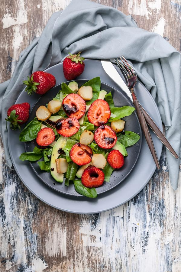 Top view tasty salad with greens, strawberries and smoked cheese. Tasty and healthy food. Vertical shot royalty free stock photography