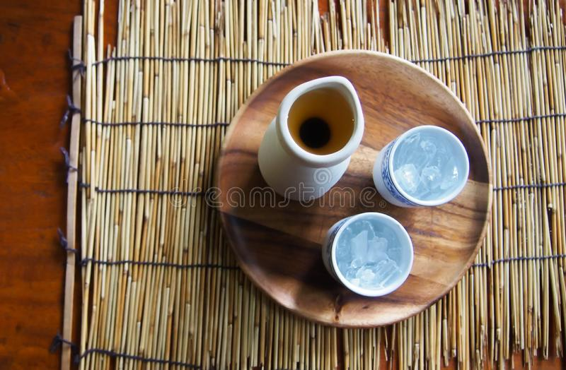 Top view of tea pot and glass of iced tea. On a wooden plate, which is placed on a bamboo mat and on a table stock photo