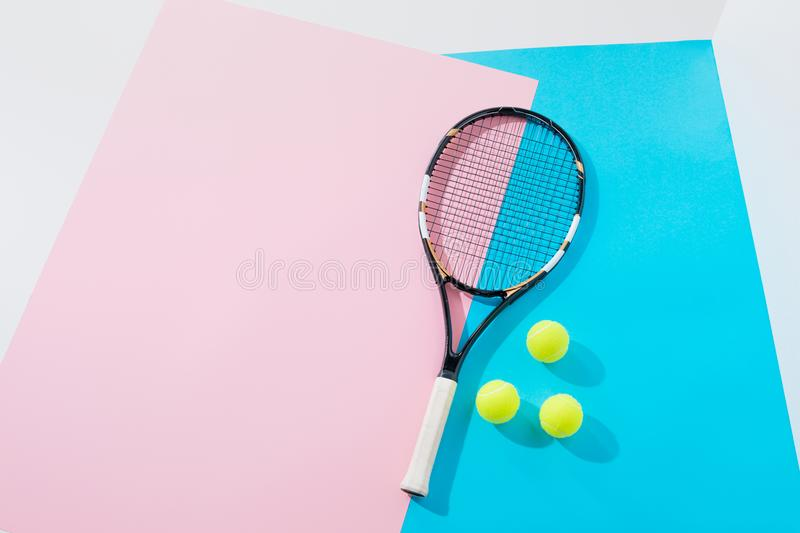 top view of tennis racket and yellow balls on blue royalty free stock photography