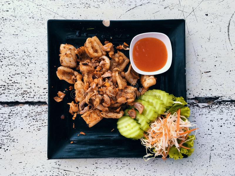 Top view Thai food fried squid in a black dish. Thai food fried squid in a black dish stock photo
