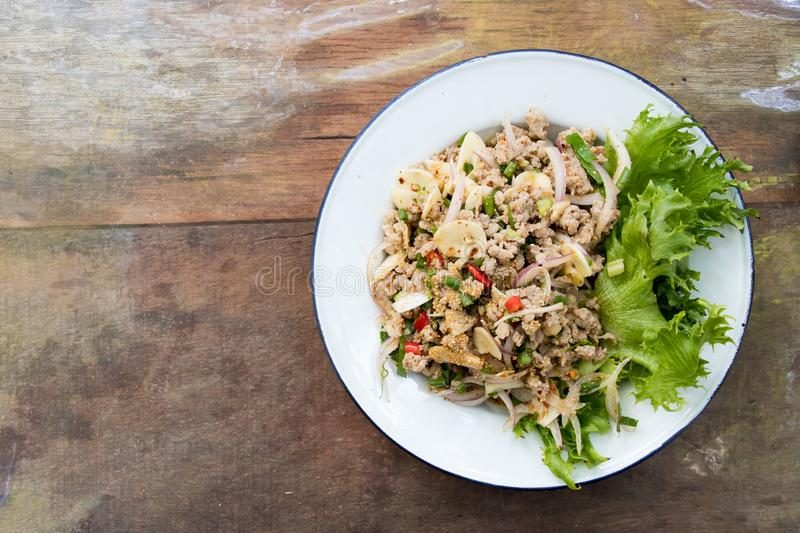 Top view of Thai food spicy minced pork salad on wood background royalty free stock photo
