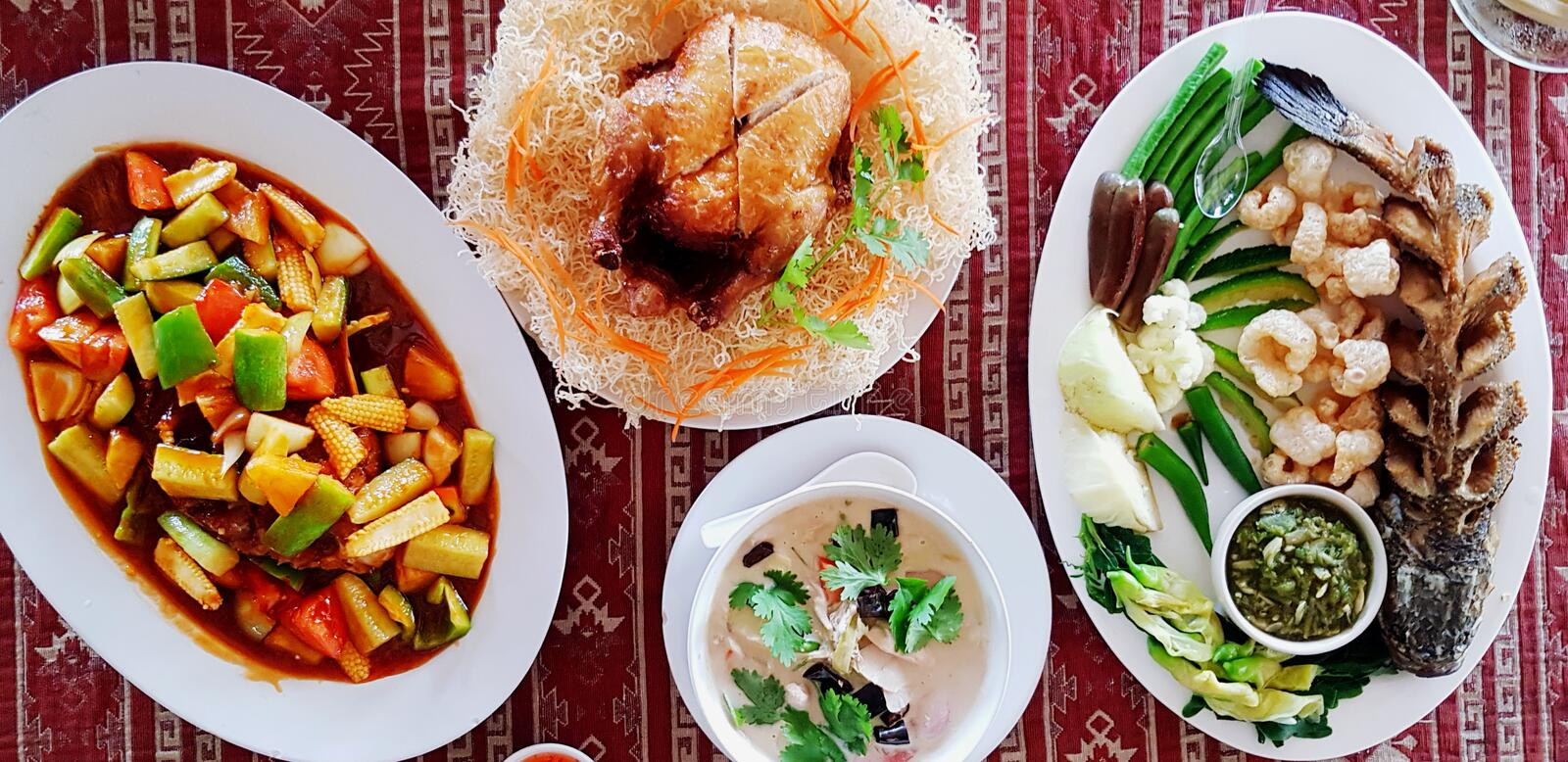 Top view of Thai food with whole baked chicken, steamed fish with green hot chili spicy sauce, coconut milk soup royalty free stock photography