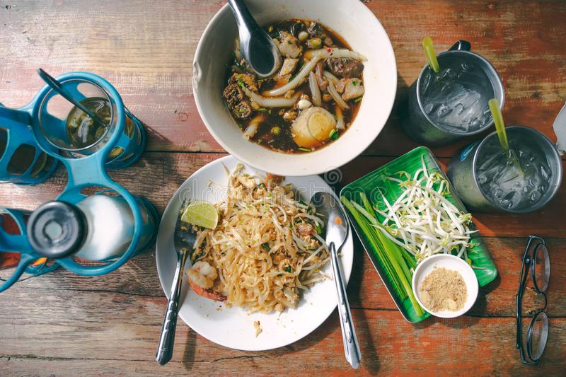 Top view thai street food on old wooden table padthai and guay jub noodle, popular traditional thai dish royalty free stock images