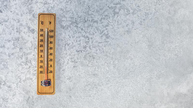 Top view on thermometer laying on layer of ice, showing temperature as low as -20 degrees Celsius. Concept illustrating extreme c. Old freezing weather in winter royalty free stock image