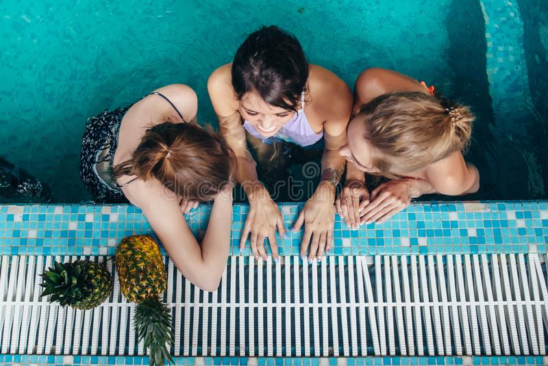 Top view of three female swimmers sitting in a swimming pool resting after training and gossiping stock photos