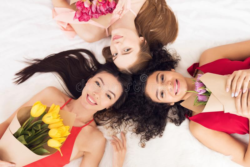 Top view three girls lying on bed with flowers. They are celebrating women`s day March 8. Top view three girls in white and red dresses lying on bed with royalty free stock photo