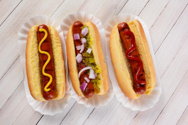 Three hot dogs on a wood table with different condiments stock image