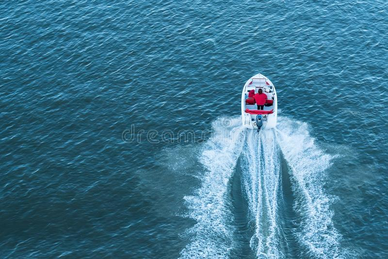 Top view of people in small motor boat on river royalty free stock image