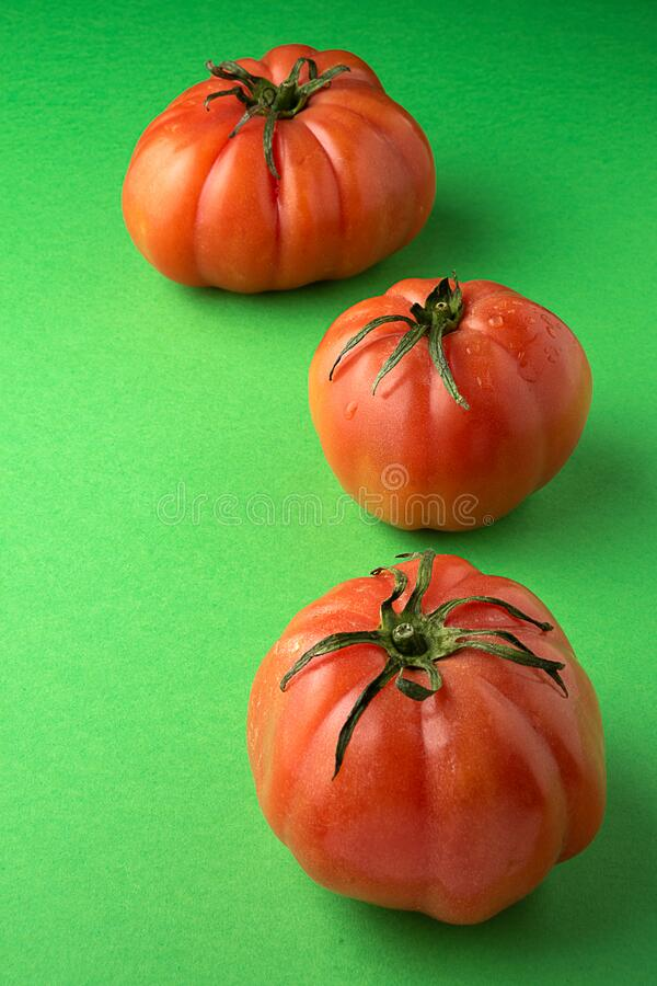 Top view of three pink tomatoes on green background in vertical royalty free stock photo