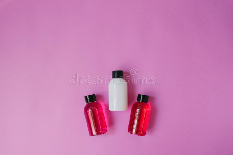 Top view of three small bottles of white and crimson and body and hair care products on top of a pink background. stock images