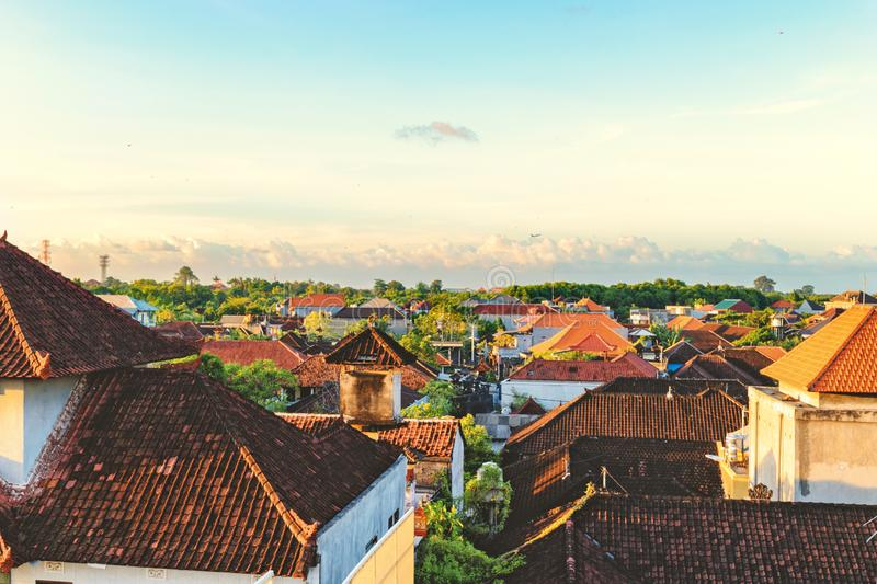 Top view of tiled roofs. Bali houses. Sunset at cozy small town. royalty free stock photo