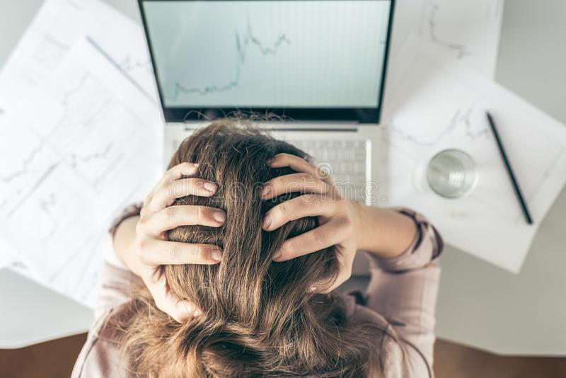 Top view. Tired business woman with headache at office with glass of water and pill on the background of graphics and charts print royalty free stock image